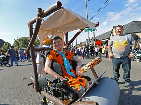 """Ryan Parker dressed as Fred Flintstone in his primitive vehicle, at the Historic Irvington Halloween Festival street fair, Indianapolis, Saturday, October 29, 2016. Parker's mother Mishell, who created the costume, said, """"after 22 years, we've mastered making wheel chair costumes."""""""