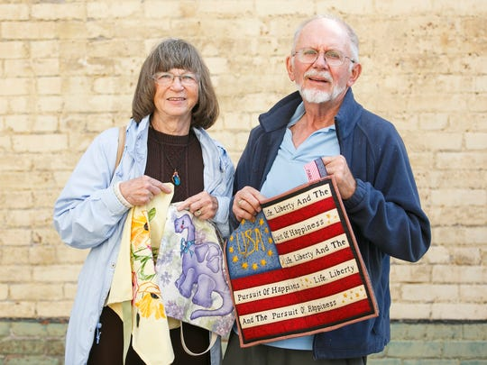 John Francis and Caye Poe hold bags designed by Poe's great-granddaughter, Alisha Payne, at Holding Court. The bags will be sold at the Hearts and Hands Exhibition at Center 50+ this weekend.