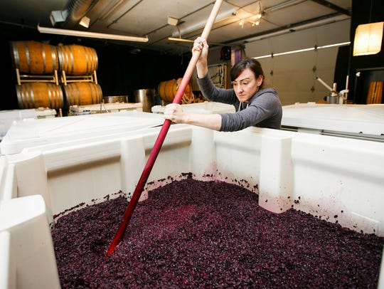 Michelle Wasner punches down grapes as Seufert Winery