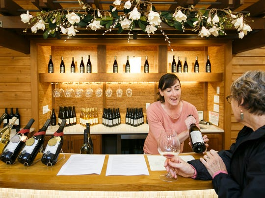 Michelle Wasner discusses Seufert Winery's pinot noir in the winery's tasting room in Dayton. Wasner and her husband own the winery and craft their award-winning wines in a small space across the town square from the tasting room.
