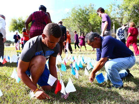 Attendees of Del Mar College's Memorial Flag Garden ceremony place flags in the garden Monday, Nov. 7, 2016.