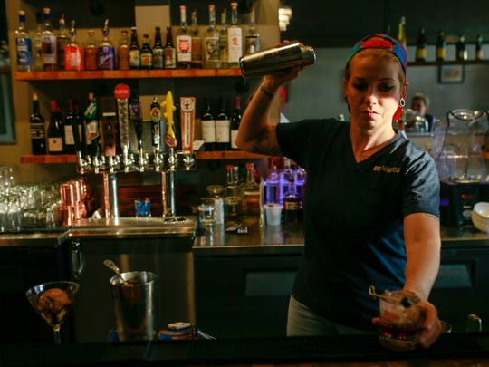 Kim Kelly, 26, of Wixom, makes drinks at the bar at Browndog Creamery and Dessert Bar in Farmington, Mich. on Tuesday, Nov. 8, 2016.