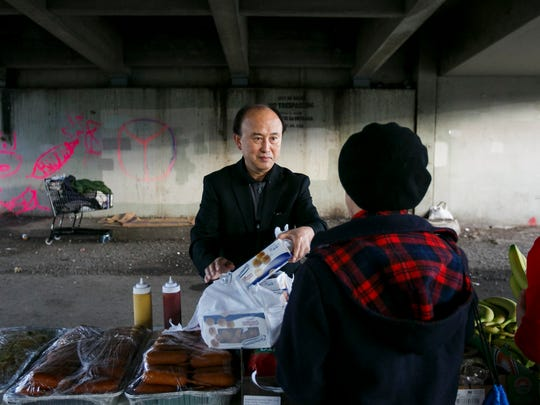 David Jeon, pastor of the Korean Church of Salem, helps other volunteers set up a table of food cooked by Korean restaurant Happy Bi Bim Bap House under the Marion Street Bridge on Monday, Nov. 7, 2016. Jeon volunteers at the weekly dinner whenever he is able.