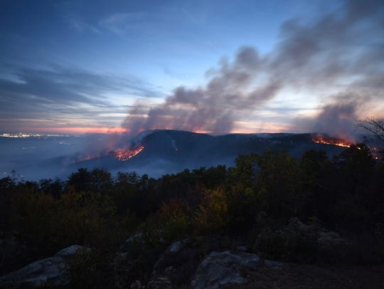 In this Nov. 7, 2016, photo, two major fires burn at