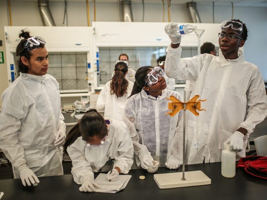 Research apprentices mix chemicals at an After Class Matters health sciences class at Malcolm X College in Chicago. The class includes students who are considering medical careers.