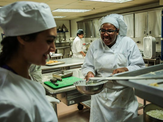 The culinary experience in the Chicago-based After Class Matters program has apprentices preparing and serving food to customers who pay $15 to $20 to eat. It benefits from a partnership with restaurants, which share their recipes and often the expertise of their chefs. Here, Chicago teens Isabel Orellana, left, and Yasmine McCoy make each other laugh while cooking in the kitchen.