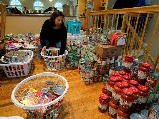 Jamie Bruno of Manalapan, who assembles and distributes baskets of food for Thanksgiving dinners to the area's needy, prepares baskets at her home  in Manalapan, NJ Wednesday, November 16, 2016.