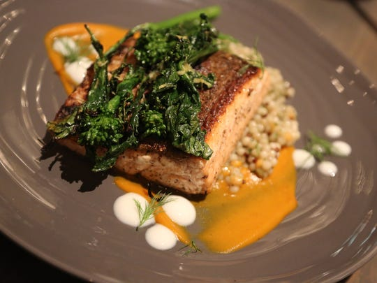 Crispy-skinned King salmon with Israeli cous cous, grilled rapini, carrot puree and yogurt from Parc, anew restaurant debuting in Detroit's Campus Martius Park Monday, November 21.