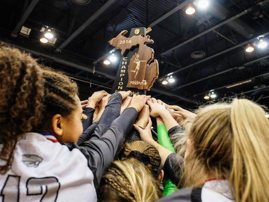 Novi players hoist the Class A girls volleyball state