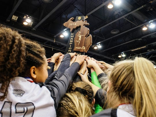 Novi players hoist the Class A girls volleyball state championship trophy for the second straight year.