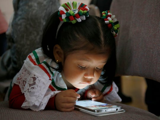 Andrea Sofia Hernandez, 2, watches a video on her mother's cell phone during the second annual Holy Mole contest.
