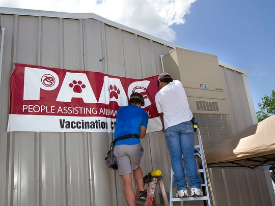 Workers get the PAAC banner up at the building that will contain the vaccination clinic at the location which will also have another building run by the Cattery that will offer low cost spay and neutering services at the PAAC opening in Corpus Christi, Saturday,  June 14, 2014.
