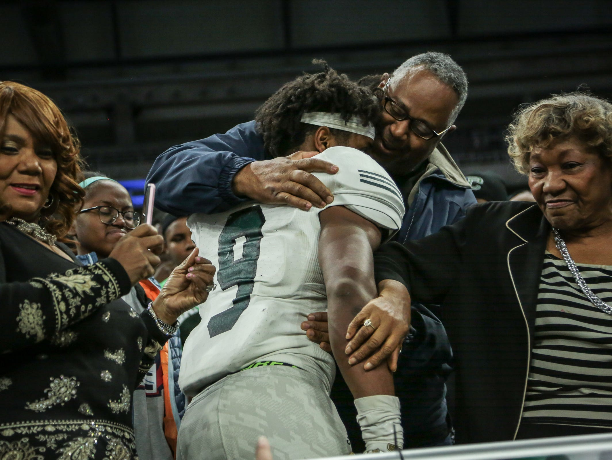 Detroit Cass Tech's Donovan Peoples-Jones (9) hugs family members after winning the title against Detroit Catholic Central during the Division 1 High School Championship game on Saturday November 26, 2016, at Ford Field in Detroit, MI.