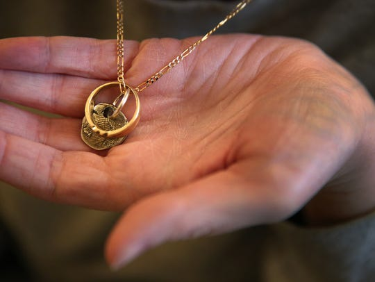 Luci Goss shows a necklace she always wears, Thursday,