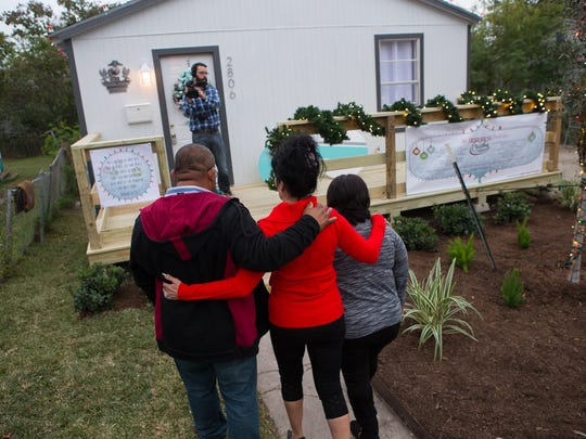 Catherine Albert (center), walks Evelia and Francisco Serna into their home Saturday, Dec. 10, 2016, to reveal the results of its Extreme Christmas Makeover.