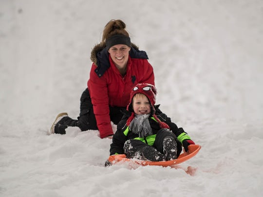 Xavier Hoxie, 4, and his mother Amanda enjoy sledding on a snow day at Leila Arboretum on Monday.
