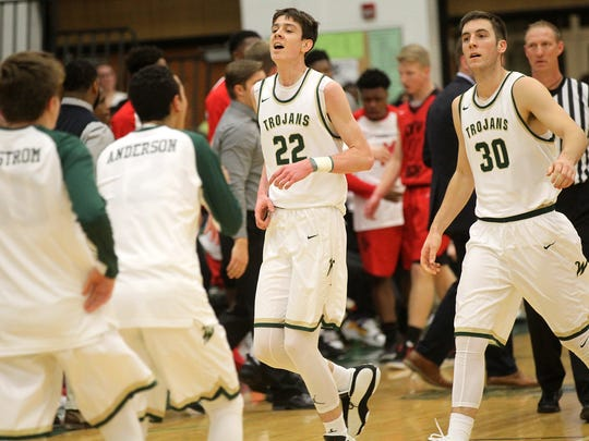 West High's Patrick McCaffery (22) and Connor McCaffery head into a timeout during their game against City High at West High on Tuesday, Dec. 13, 2016.