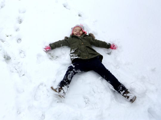 Isabella Farley-Soto, 3, makes a snow angel outside her home in Independence on Thursday, Dec. 15, 2016.