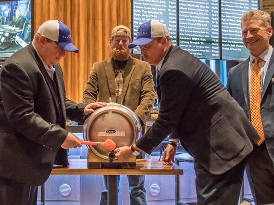 NHBP Tribal Council Chairman Jamie Stuck taps a keg Thursday with assistance from Bryan Wiggs of Dark Horse Brewing Co., center, and Tribal Council Treasurer Tony Day at Dacey's Taphouse within FireKeepers Casino Hotel in Emmett Township.