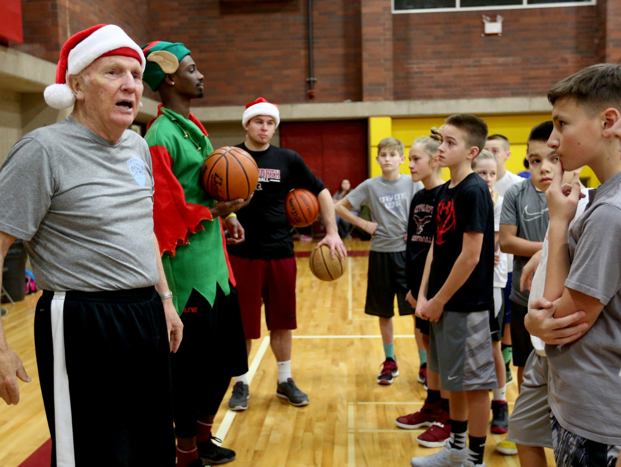Barry Adams, left, a National Coaches Association Hall of Fame inductee and former South Salem basketball coach, leads a session during the free kid's basketball clinic, part of the Capitol City Classic tournament, at Willamette University in Salem on Thursday, Dec. 22, 2016.