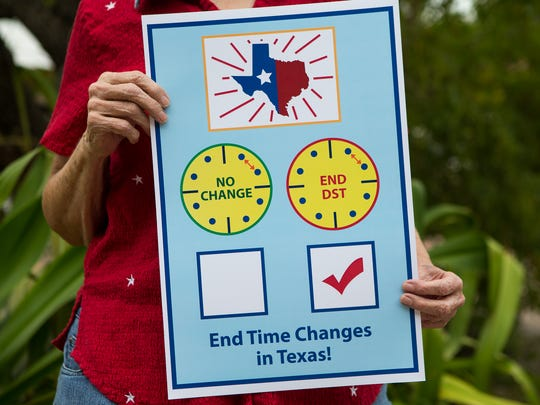 Martha Habluetzel who is campaigning for Texas to end  daylight saving time holds one of her signs outside her  Ingleside home.