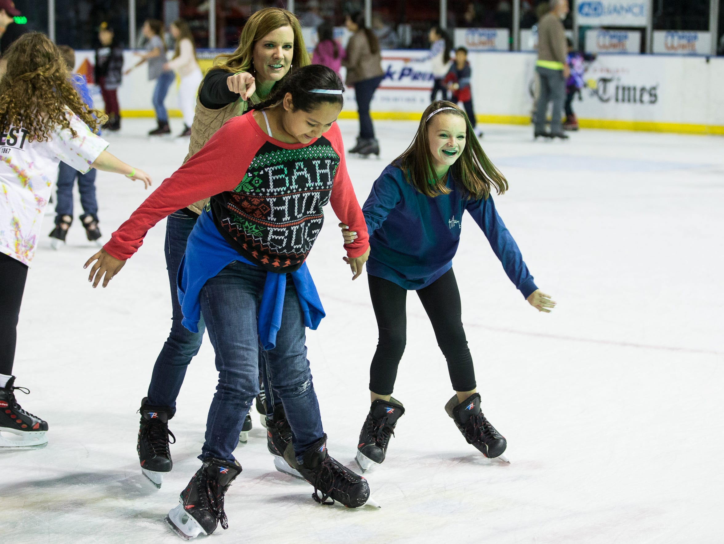 People skate on the ice during American Bank Center's