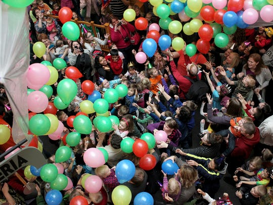 Kids and parents reach for falling balloons Monday