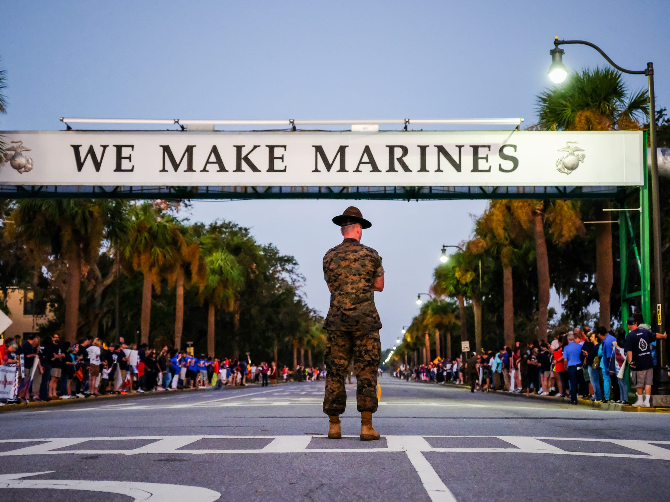 """A drill instructor stands in the middle of the road before daylight outside the Parris Island visitor's center, with families lined up to watch, officers, instructors and new Marines run a 3-mile """"motivational run"""" the day before graduation on Wednesday October 19, 2016 at the Marine Corps Recruit Depot in Parris Island, SC."""