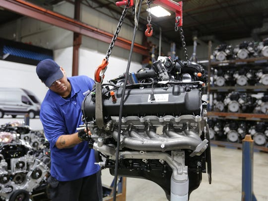 A worker at Roush CleanTech installs propane components onto a 6.8-liter, V10 engine manufactured by Ford so it can run on propane at the company's plant in Livonia.