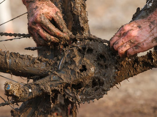 A cyclist fixes his bike during the Jingle Cross World