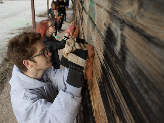 Noah Collins, 15, scrubs at graffiti. He was one of