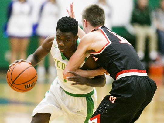 McKay's Shaton Daniels (1) pushes past McMinnville's Parker Spence (12) on Tuesday, Jan. 3, 2017, at McKay High School. Daniels scored 19 points in the Royal Scots' 80-79 victory.