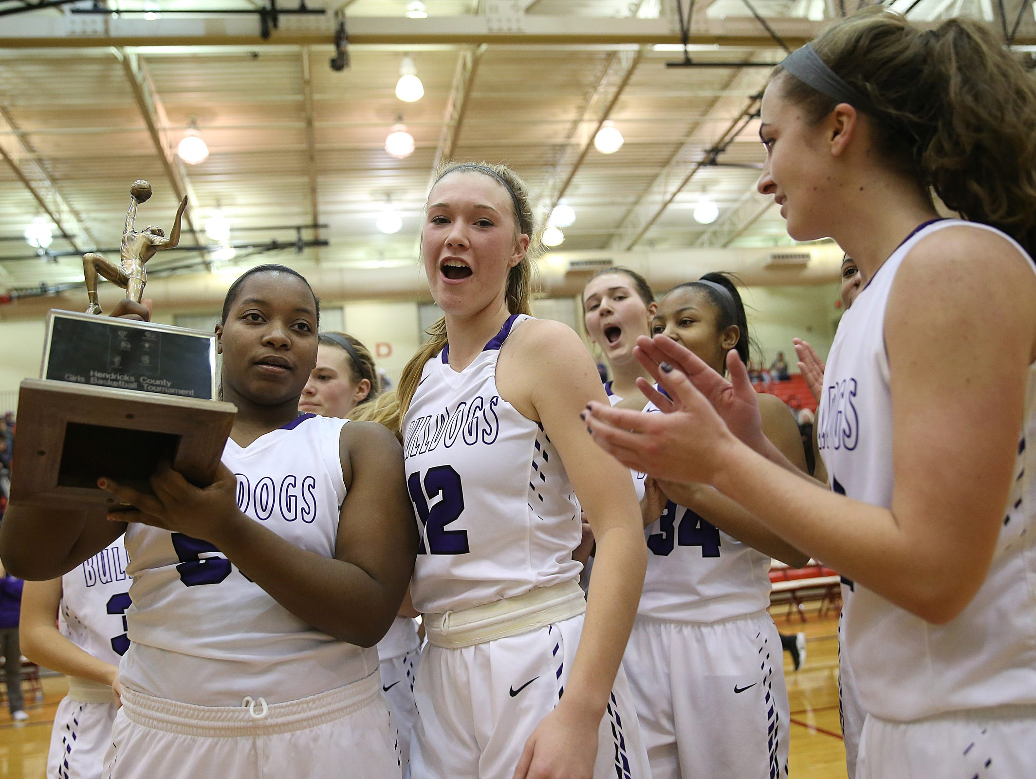 The Brownsburg Bulldogs celebrate with the trophy after defeating Danville in Hendricks County girls basketball finals at Plainfield High School, Plainfield, Ind., Saturday, Jan. 7, 2016. Brownsburg won, 46-40.