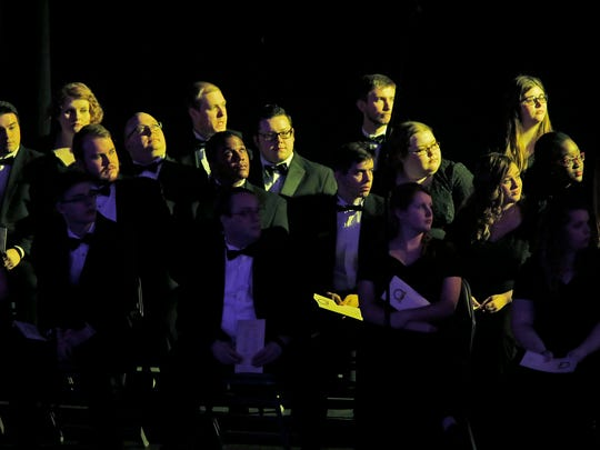 "The Hanover College Concert Choir is bathed in yellow stage light before singing ""Back Home Again in Indiana,"" during the Inauguration ceremony at the Indiana Gubernatorial Indiana State Fairgrounds, Monday, January 9, 2017."