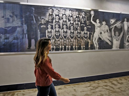 Samantha Smith walks through the hall, passing historic photos, at Butler University's Hinkle Fieldhouse, Monday, January 2, 2017, thinking of a year without her husband Andrew.  Former Butler University basketball player Andrew Smith died January 12, 2016, after a long, public battle with non-Hodgkin lymphoma, and later leukemia.