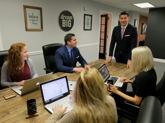 John A. Vagueiro, president of Adapting Social, a business that helps other businesses with social marketing, works with some of the members of his team in Red Bank.