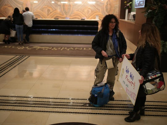Mirriam Halprian, 50, left, and Nina Robb, 59, both from Bloomfield Township, MI wait with others inside the MGM Grand Casino lobby on Friday, January 20, 2017 in Detroit in hopes for a bus to show up to give them a ride to the Women March in Washington. After sending $K to a bus company in Pennsylvania and the bus not showing up, they think it was an Internet swindle.