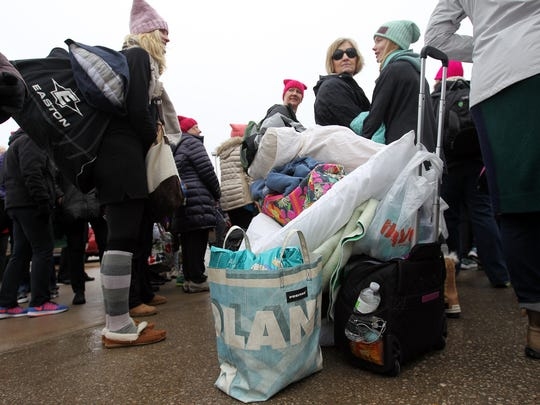 Pillows and bags are stacked up as women wait for their