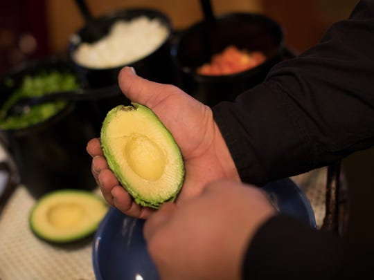 Paul Rowland manager of Senor Jaime's scopes out the meat of an avocado as he makes fresh guacamole table side.