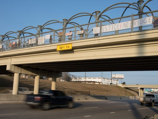Hillcrest residents and advocates hold signs from the Alameda Street bridge as they rally regarding the voluntary relocation program on Monday, Feb. 6, 2017.