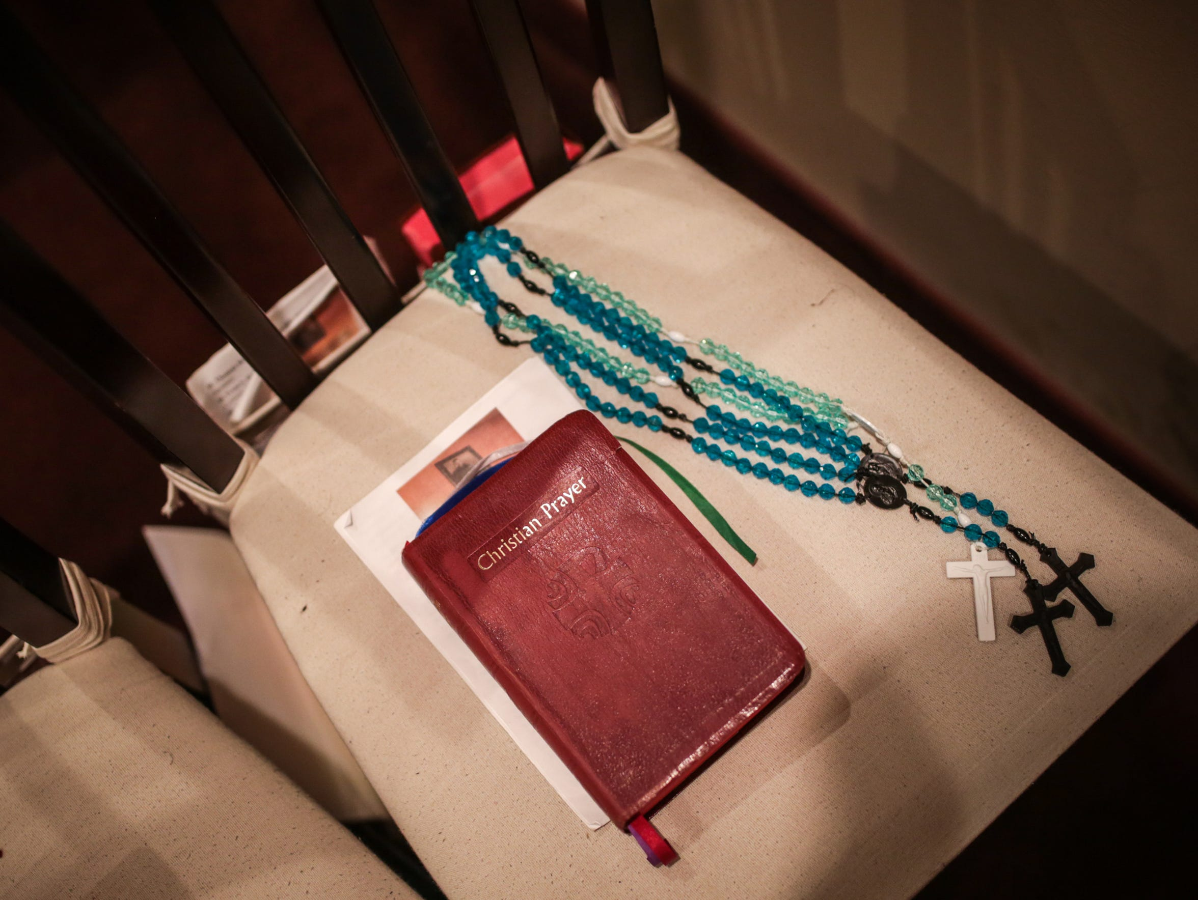 A Christian Prayer book and prying rosaries are seen