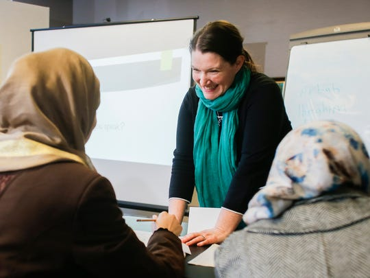 Erika Brown-Binion, Director of the Refugee Development Center in Lansing assists Syrian refugees Feb. 10, 2017, during an afternoon class helping adult students with their English language skills.    Community members from Syria, Jordan, Nepal, and Sudan were present.