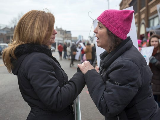 Andrea Rofe, 40, of Sylvan Lake, left, is stopped by