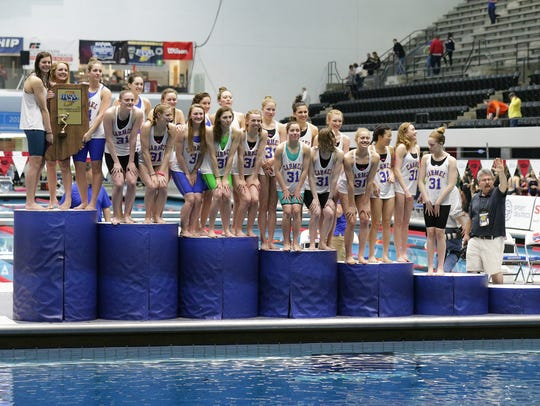 The Carmel Girls Swim Team is presented a trophy for