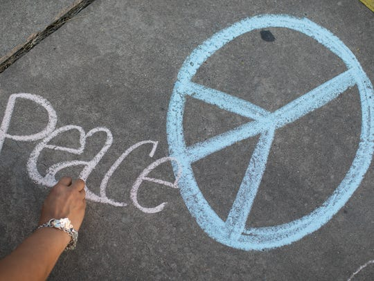 """A participant uses chalk to write """"Peace"""" on the pavement"""