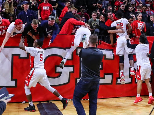 Rutgers players climb into the student section after