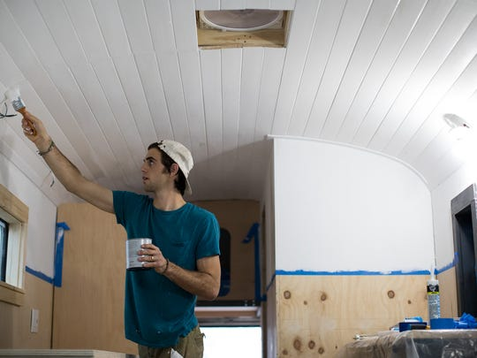 Chad Schirmer paints the ceiling of a former prison bus he and his wife are retrofitting to use as their home in February  2017.