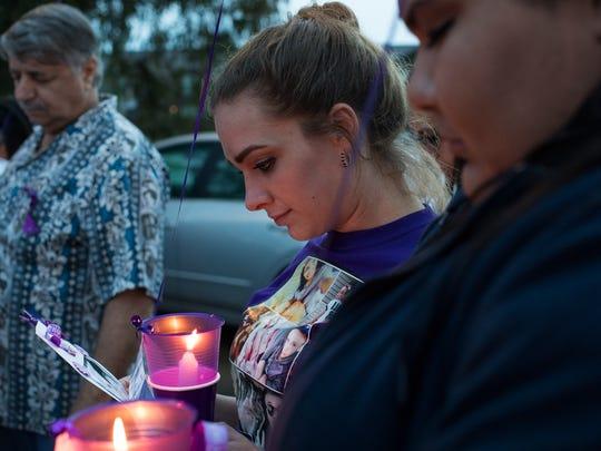 Lauren Felts bows her head during a vigil at the Corpus
