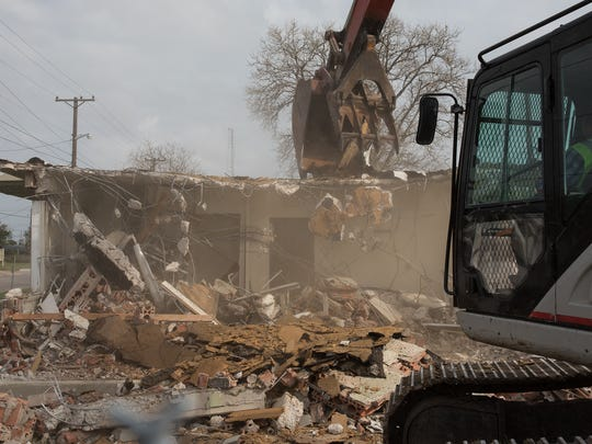 Th first unit of the D.N. Leathers housing public housing complex, built in 1940, is torn down Monday. It's expected the entire demolition of the property will take 45 days.