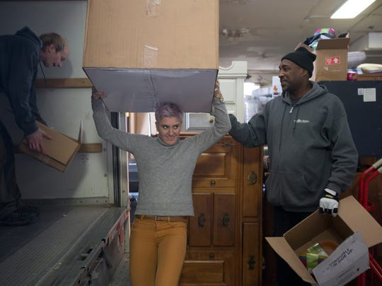 From left, mover Alex Heffernan, 27, organizes boxes